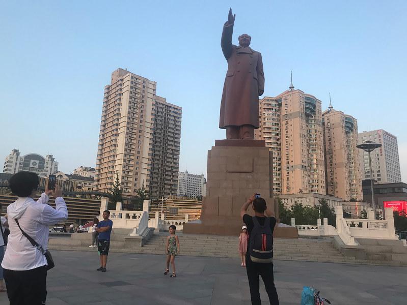毛沢東像がそびえる丹東駅前。市内には高層マンションが林立する(筆者撮影)
