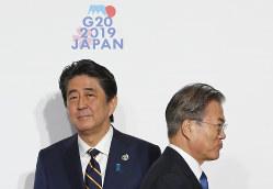 安倍晋三首相(左)も韓国の文在寅大統領も大局に立った判断ができるか(大阪市で6月28日)(Bloomberg)
