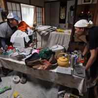 大雨被害から一夜が明け、浸水した自宅の居間を片付ける岩崎高久さん(右)、博文さん兄弟=佐賀県武雄市北方町で2019年8月29日午前10時3分、森園道子撮影