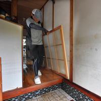 大雨被害から一夜が明け、浸水した自宅から家財道具を運び出す岩崎博文さん。玄関の壁には1990年の豪雨の際の浸水時の線(中央下)の上に、今回の浸水の痕跡が帯状に残る=佐賀県武雄市北方町で2019年8月29日午前9時58分、森園道子撮影