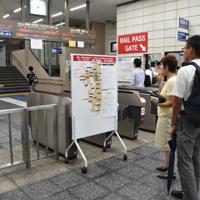 大雨から一夜明けたJR佐賀駅で列車の運行情報を見つめる利用客ら=2019年8月29日午前7時27分、山口響撮影