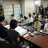 集まった署名の一部を持参して記者会見する松永さんの夫(手前左から2人目)=東京・霞が関の司法記者クラブで2019年8月30日午後6時13分、小川昌宏撮影