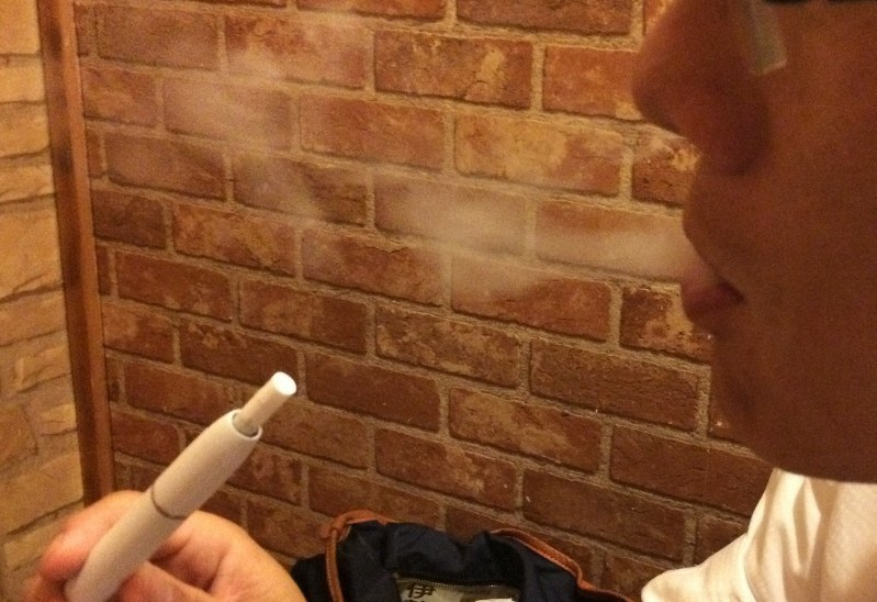 加熱式たばこを吸って蒸気を吐き出す男性=久保聡撮影