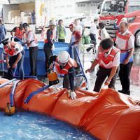 訓練で小型排水ポンプを使って、たまった水を吸い上げる関係者=関西国際空港で2019年7月、幾島健太郎撮影