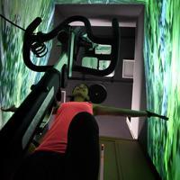 1人でトレーニングできる「個ジム」。個室の壁に映像が流れ、フィットネスバイクをこぐと自然の中をサイクリングしているような気分が味わえる=横浜市港南区で2019年7月、竹内紀臣撮影
