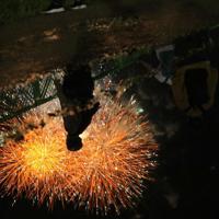 夕方に振った雨でできた水たまりのそばで「大曲の花火」を見つめる人たち=秋田県大仙市で2019年8月31日午後8時46分、和田大典撮影