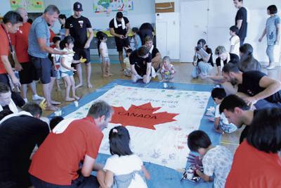 盛岡市内の保育園児たちと応援フラッグを作るカナダ水球男子の選手たち=盛岡市のくりやがわ保育園で(盛岡市提供)