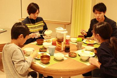 「第三の居場所」でスタッフと一緒に食事をする子どもたち=日本財団提供