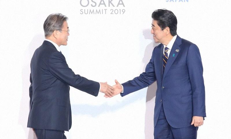 韓国の文在寅大統領(左)を出迎える安倍首相(6月28日午前11時30分、大阪市住之江区で)=代表撮影