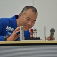 実際に衛星に搭載されるガンダムとシャアザクに笑顔で見入る宇宙飛行士の野口聡一さん=静岡市葵区のバンダイホビーセンターで2019年9月4日午後2時2分、高場悠撮影