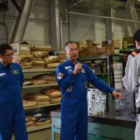 ガンプラの金型工場を視察する宇宙飛行士の金井宣茂さん(左)と野口聡一さん(中央)=2019年9月4日午後1時16分、高場悠撮影