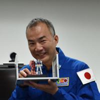 衛星に搭載されるガンダムとシャアザクを手に持ち笑顔の野口聡一さん=静岡市葵区のバンダイホビーセンターで2019年9月4日午後2時24分、高場悠撮影