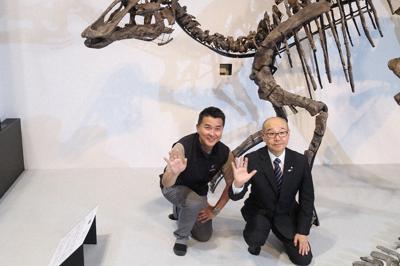 「カムイサウルス・ジャポニクス」の化石や複製骨格の横で、手を上げる竹中喜之・北海道むかわ町長(右)と、化石を分析した小林快次・北海道大教授=東京都台東区の国立科学博物館で2019年9月4日、永山悦子撮影