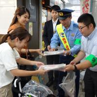 通行人の女性に痴漢への注意を呼びかけるチラシを配る葛西署員ら=江戸川区西葛西の西葛西駅で