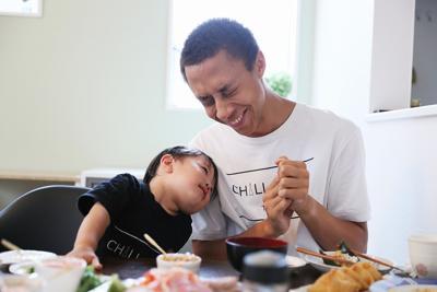 ホームシェアサービス「ホーミー」を利用して麻生芳明さん宅の一部屋に住むマーカス・ジャクソンさん(右)。週末に麻生さん家族とお昼ご飯を食べている最中、麻生さんの息子の泰志くんがマーカスさんにもたれかかる=東京都杉並区で2019年9月1日、吉田航太撮影
