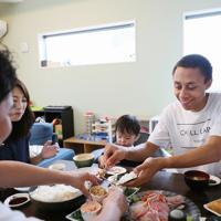 ホームシェアサービス「ホーミー」を利用して麻生芳明さん(左手前)宅の一部屋に住むマーカス・ジャクソンさん(右)。週末のお昼に麻生さんと妻の天美さん(左奧)、息子の泰志くんと一緒に昼食を食べる=東京都杉並区で2019年9月1日、吉田航太撮影