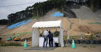 A couple offers flowers on a table for the victims of a powerful earthquake that struck Hokkaido and claimed 44 lives, in front of a site where reconstruction work continues in the prefecture town of Atsuma on Sept. 6, 2019, the first anniversary of the disaster. (Mainichi/Taichi Kaizuka)