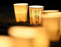 Candles are lit in cups with messages for the victims of a powerful earthquake that struck Hokkaido, in front of the Atsuma Town Government's office before dawn on Sept. 6, 2019, the first anniversary of the disaster. (Mainichi/Taichi Kaizuka)