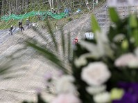Workers are seen at the rear continuing reconstruction work at a site where a landslide occurred due to a powerful earthquake that struck Hokkaido as a bouquet of flowers sits on a table for the victims in the prefecture town of Atsuma on Sept. 6, 2019, the first anniversary of the disaster. (Mainichi/Taichi Kaizuka)