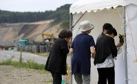 People visit a site to offer flowers for the victims of a powerful earthquake that struck Hokkaido, in the prefecture town of Atsuma on Sept. 6, 2019, the first anniversary of the disaster, as a reconstruction site can be seen in the rear. (Mainichi/Taichi Kaizuka)