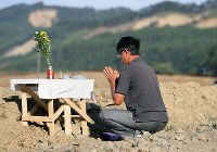Takashi Yamamoto, who lost three members of his family to the deadly earthquake that struck Hokkaido, prays for them at a site where they died in the prefecture town of Atsuma on Sept. 6, 2019, the first anniversary of the disaster. (Mainichi/Taichi Kaizuka)