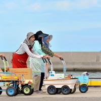 オンバを押しながら談笑する島のおばあちゃんたち=高松市男木町で、山田尚弘撮影
