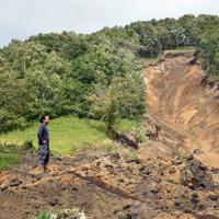 地震で崩れた山の土砂に埋まった幌里地区を眺める小林廉さん。舗装道路が跡形も無くなっていた=北海道厚真町で2018年9月12日、北山夏帆撮影