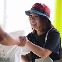 札幌市の青空に出店した「小林農園」の卵を購入する女性。道内のあちこちから人が集まる=同市北区で2019年8月18日、北山夏帆撮影