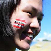 ラグビーW杯決起会で、頰に「ONE TEAM」の文字が書かれたシールを貼り笑顔を見せる女性=東京・秩父宮ラグビー場で2019年9月7日、竹内紀臣撮影