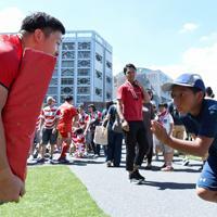 ラグビーW杯決起会会場に特設されたラグビー体験ブースで、ラグビー選手にタックルする男の子(右)=東京・秩父宮ラグビー場で2019年9月7日、竹内紀臣撮影