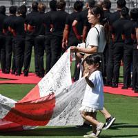 ラグビーW杯決起会で、日本代表への応援メッセージが書かれた旗を手を振りながら運ぶ女の子ら=東京・秩父宮ラグビー場で2019年9月7日、竹内紀臣撮影