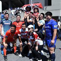 ラグビーW杯決起会会場に特設されたラグビー体験ブースで、ラグビー選手と並んで記念撮影をする人たち=東京・秩父宮ラグビー場で2019年9月7日、竹内紀臣撮影