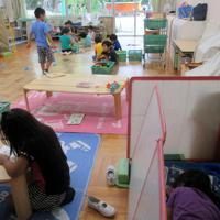 午後に自由遊びをする4、5歳児クラスの子どもたち。昼寝をしたい子(右手前)は部屋の一角についたてを置いて横になる=鹿浜こども園で(同園提供)
