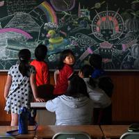 アヒルや戦車の上のすし、時計。大学生たちが7時間かけて制作した幻想的な絵を前に、子供たちは熱心に話し合った=中札内小で