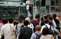 People form a long line as they wait to ride a bus in Tokyo's Shibuya Ward after the capital's train network fell into chaos due to powerful Typhoon Faxai on the morning of Sept. 9, 2019. (Mainichi/Shinnosuke Kyan)