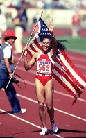 1988 Seoul Olympics -- Florence Joyner, of the United States, celebrates her success as she carries her country's national flag.