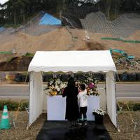 復旧活動が続く吉野地区に設置された献花台を訪れ、花を供える遺族=北海道厚真町で2019年9月6日午後5時32分、貝塚太一撮影