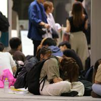 建物の下で雨をしのぎながら電車の再開を待つ人たち=東京都渋谷区で2019年9月9日午前7時35分、喜屋武真之介撮影