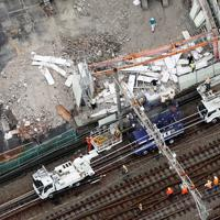 台風15号の影響で線路側に倒れた工事現場の外壁を撤去する作業車=横浜市旭区で2019年9月9日午前9時、本社ヘリから玉城達郎撮影