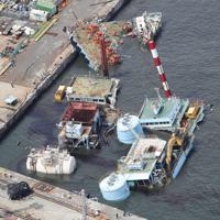 台風15号の影響で沈みかけた台船。油のようなものが海面に浮いていた=横浜市中区で2019年9月9日午前10時42分、本社ヘリから玉城達郎撮影