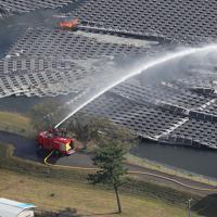 懸命な消火活動が続けられる山倉ダムの湖面に浮かべられたソーラーパネル=千葉県市原市で2019年9月9日午後2時48分、本社ヘリから玉城達郎撮影