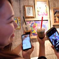 買ったばかりのタピオカドリンクをスマートフォンで撮影する人たち=大阪市北区で2019年8月30日午前11時12分、小松雄介撮影