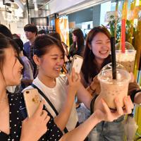 買ったばかりのタピオカドリンクをスマートフォンで撮影する女性ら=大阪市北区で2019年8月30日午前11時12分、小松雄介撮影