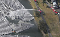 Firefighting efforts to put out a blaze involving solar panels installed on the surface of the lake at Yamakura Dam are seen from a Mainichi Shimbun helicopter after Typhoon Faxai struck the city of Ichihara, Chiba Prefecture, on Sept. 9, 2019. (Mainichi/Tatsuro Tamaki)