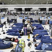 出発ロビーのチェックインカウンター前で、寝袋を使って横になる利用客=成田空港で2019年9月10日午前4時13分、藤井達也撮影