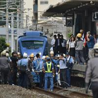 JR東福間駅構内の線路に落ちた軽乗用車を取り囲む関係者。後ろは緊急停車した特急ソニック=福岡県福津市で2019年9月6日午後3時47分、田鍋公也撮影