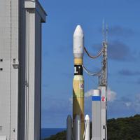 組み立て棟(左)から発射台に移動するH2Bロケット=鹿児島県南種子町の種子島宇宙センターで2019年9月10日午後2時34分、徳野仁子撮影