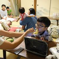 自宅が停電、断水し、避難所で過ごす親子。仙台市で東日本大震災に遭った女性(手前)は「夏の停電は、暑い中、クーラーや冷蔵庫、お風呂が使えないことがつらいです」と話していた=千葉市若葉区で2019年9月10日午後7時7分、丸山博撮影