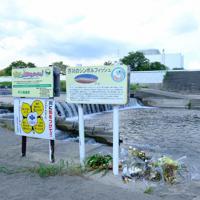 事故現場では既存の看板の下に「川に気をつけて」と書かれた看板が新たに設置され、花も供えられている=大阪府高槻市で2019年9月10日午後1時36分、土田暁彦撮影