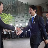 首相官邸に入り留任が内定した麻生太郎副総理兼財務相(左)と握手する環境相に就任が内定した小泉進次郎氏(右)=2019年9月11日午後1時24分、川田雅浩撮影
